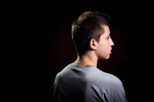 White Male Teen In Grey T-Shirt With Back Turned Away In Front Of A Black Background